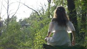 Frau, die in Yogalotussitz sitzt und die Natur im Freien erwägt - stock footage