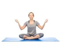 Frau, die Yogameditation in der Lotoshaltung auf Matte macht Stockbild