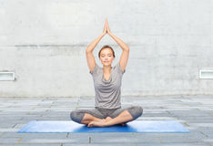 Frau, die Yogameditation in der Lotoshaltung auf Matte macht Stockfotografie