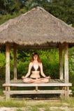 Frau, die Yogameditation im tropischen Gazebo tut Stockbild