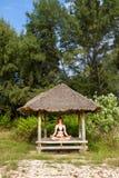 Frau, die Yogameditation im tropischen Gazebo tut Stockfotos