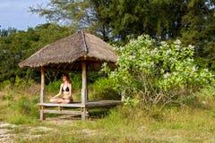 Frau, die Yogameditation im tropischen Gazebo tut Stockfotografie