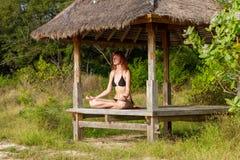 Frau, die Yogameditation im tropischen Gazebo tut Stockfoto
