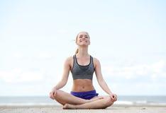 Frau, die in Yogaposition sitzt und draußen lächelt Stockfotografie
