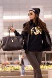 Frau, die Yves Saint Laurent Black-T-Shirt u. -handtasche trägt Lizenzfreie Stockfotografie