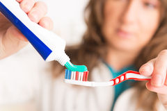Frau, die Zahnbürste und Zahnpasta hält Stockbild