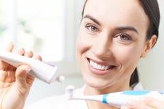 Frau, die Zahnpasta auf elektrische Zahnbürste im Badezimmer zusammendrückt stockfotos