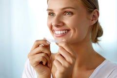 Frau, die Zahnweißungs-Streifen für schönes weißes Lächeln verwendet stockbilder
