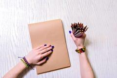 Frau, die Zeichenstifte und Notizbuch hält Stockbild