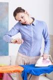 Frau, die Zeit während der bügelnden Kleidung überprüft Lizenzfreie Stockfotos