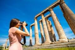 Frau, die Zeus-Tempel in der Akropolise fotografiert Stockfotografie