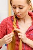 Frau, die Zopf auf blondem Haar tut Lizenzfreie Stockbilder