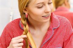Frau, die Zopf auf blondem Haar tut Lizenzfreies Stockfoto