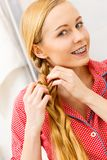 Frau, die Zopf auf blondem Haar tut Lizenzfreies Stockbild