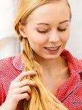 Frau, die Zopf auf blondem Haar tut Stockfotografie