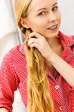 Frau, die Zopf auf blondem Haar tut Stockfoto