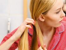 Frau, die Zopf auf blondem Haar tut Stockfotos