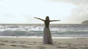 Frau, die zu den Ozean- und Erhöhungshänden in einer Luft genießt Freiheit auf Strand bei Sonnenaufgang geht stock footage