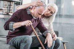 Frau, die zu Hause älteren Ehemann mit Spazierstock umarmt lizenzfreie stockfotografie