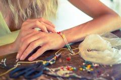 Frau, die zu Hause Armband herstellt Stockbild
