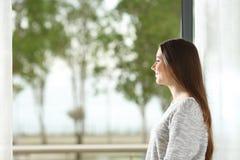 Frau, die zu Hause Außenseite durch Fenster schaut lizenzfreies stockbild