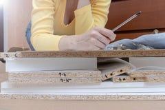 Frau, die zu Hause auf dem Boden und den zusammenbauenden Möbeln unter Verwendung der Handwerkzeuge sitzt stockfoto