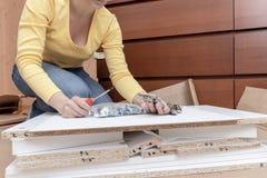 Frau, die zu Hause auf dem Boden und den zusammenbauenden Möbeln unter Verwendung der Handwerkzeuge sitzt lizenzfreie stockbilder