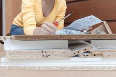Frau, die zu Hause auf dem Boden und den zusammenbauenden M?beln unter Verwendung der Handwerkzeuge sitzt lizenzfreies stockbild