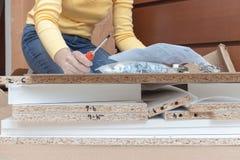 Frau, die zu Hause auf dem Boden und den zusammenbauenden M?beln unter Verwendung der Handwerkzeuge sitzt stockfotografie