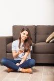 Frau, die zu Hause auf einem Smartphone simst Stockfotografie
