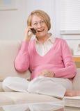 Frau, die zu Hause auf Handy auf Sofa spricht Lizenzfreie Stockfotos