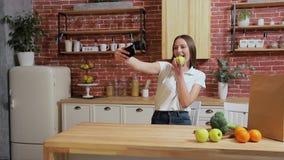 Frau, die zu Hause auf Küche des Handys grast Junge Frau, die auf dem Smartphonelächeln glücklich grast Eine Frau isst einen Apfe stock video footage