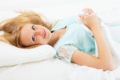 Frau, die zu Hause auf weißem Blatt im Bett liegt Stockbild