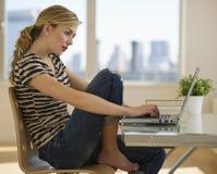 Frau, die zu Hause an Computer arbeitet Lizenzfreies Stockbild