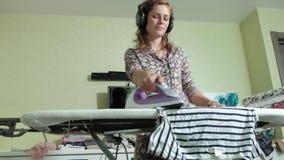 Frau, die zu Hause den Berg der Wäscherei in der Küche hört Musik auf Kopfhörern und dem Tanzen bügelt stock footage