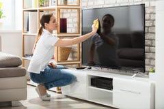 Frau, die zu Hause den Fernsehschirm abwischt Lizenzfreie Stockfotos