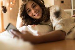 Frau, die zu Hause einen Smartphone verwendet lizenzfreies stockfoto