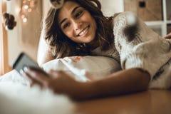 Frau, die zu Hause einen Smartphone verwendet stockfoto