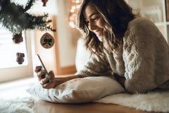 Frau, die zu Hause einen Smartphone verwendet stockfotos
