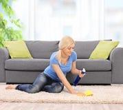 Frau, die zu Hause einen Teppich mit einem Lappen säubert Stockfoto