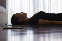 Frau, die zu Hause, hörend Musik meditiert stockfotografie