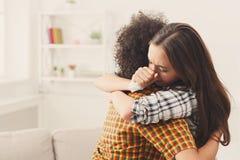Frau, die zu Hause ihren deprimierten Freund umarmt lizenzfreies stockfoto