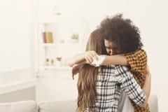 Frau, die zu Hause ihren deprimierten Freund umarmt stockbild