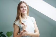 Frau, die zu Hause Kamera betrachtet Stockbilder