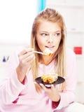 Frau, die zu Hause Kuchen isst Stockfotografie