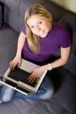 Frau, die zu Hause an Laptop arbeitet stockbild