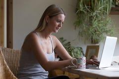 Frau, die zu Hause Laptop verwendet Stockfotografie