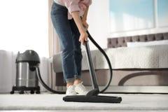 Frau, die zu Hause Schmutz vom Teppich mit Staubsauger entfernt stockbild