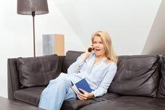 Frau, die zu Hause am Telefon spricht Lizenzfreies Stockbild