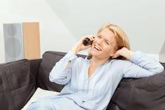 Frau, die zu Hause am Telefon spricht Stockfotografie